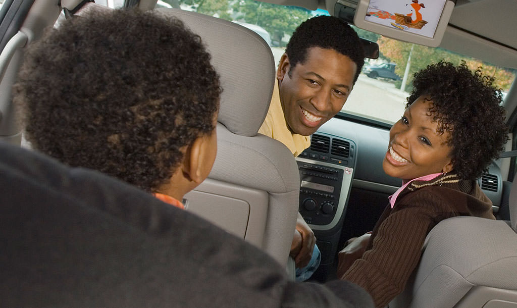 Family in car using many accessories like dvd player,  all of which drain the battery, that is why they need an AGM Battery from Johnson Controls.